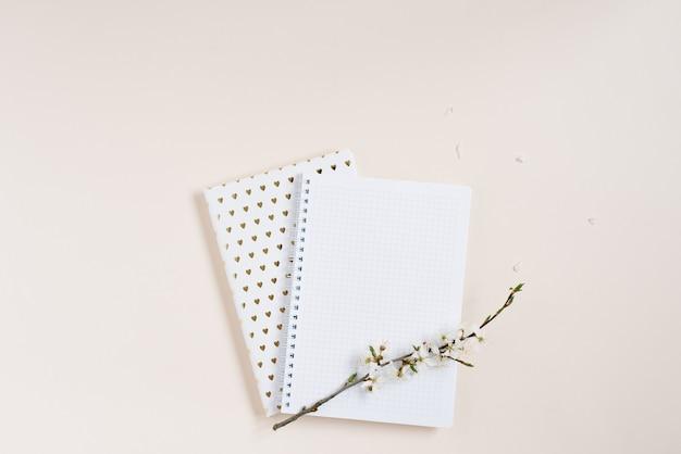 흰색 사과 꽃과 빈 시트 레이아웃이 있는 메모장의 평면 위치 구성