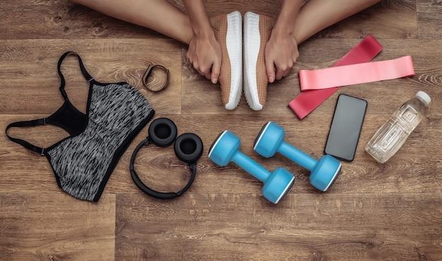 フローリングの女性の脚、スポーツ用品、衣服のフラットレイ構成。フィットネス、スポーツ、健康的なライフスタイルのコンセプト。上面図