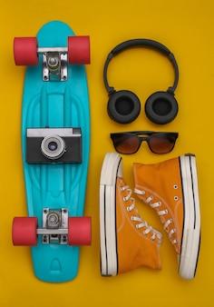 Плоская композиция из молодежных хипстерских аксессуаров. доска круизера, кроссовки, наушники, камера и солнечные очки на желтом фоне. вид сверху