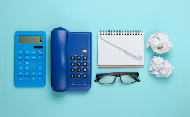 Flat lay composition of office supplies on a blue pastel