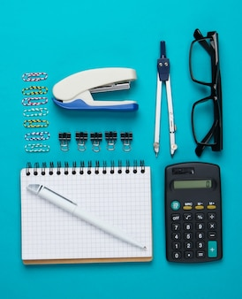 Flat lay composition of office tools, stationery on blue.