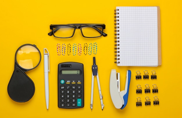 Flat lay composition of office tools, stationery on yellow.