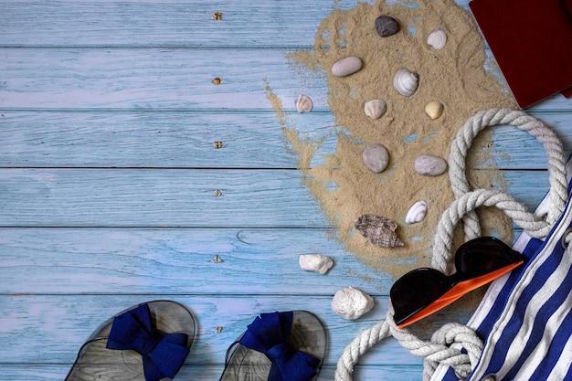 Плоская композиция на синем деревянном фоне аксессуары для летних каникул, место для вашего текста.