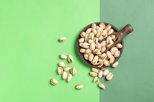 Flat lay composition of pistachios on wooden spoon and dish on green