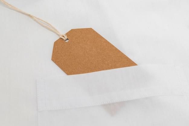 Composizione piatta laica dell'etichetta di imballaggio riciclabile sulla camicia bianca