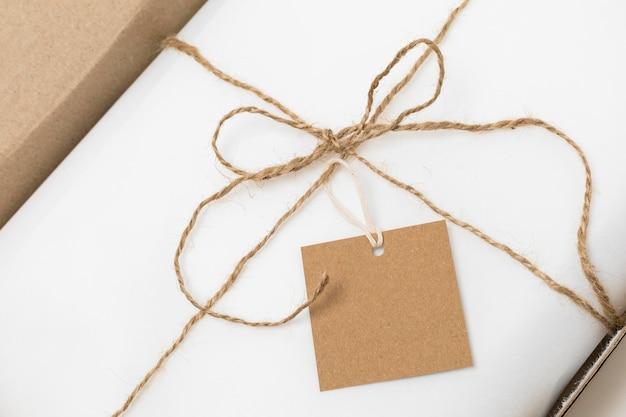 Composizione piatta laica di tag riciclabile sulla confezione bianca