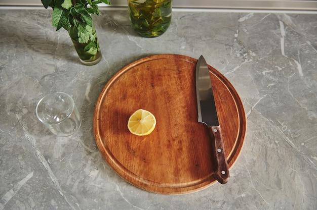 ナイフで平らに置き、台所のカウンタートップにミントが入ったガラスの近くの丸い木製の台所板にレモンを半分に切る Premium写真