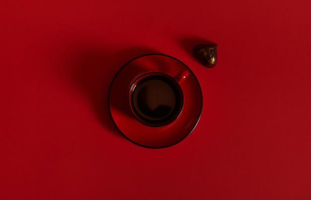 セラミック受け皿に赤い一杯のコーヒーを置き、赤い表面にハートの形をしたプラリネを入れたフラットレイコンポジション。コピースペースと赤い背景の上のチョコレートの日の概念