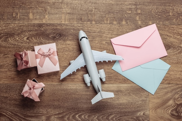 Flat lay composition with airplane figure, gift boxes and envelopes of letters on floor.