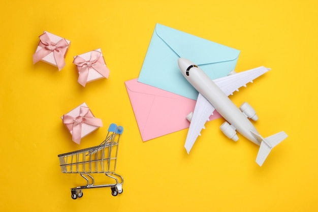 Flat lay composition with airplane figure, gift boxes, shopping trolley and envelopes of letters on yellow.