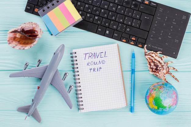 파란색 책상에 비행기, 지구, 조개, 메모장이 있는 평평한 구성. 여름 여행 개념입니다.