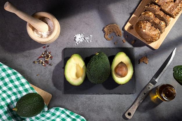 Плоская композиция с авокадо на темном столе с оконными шторами.
