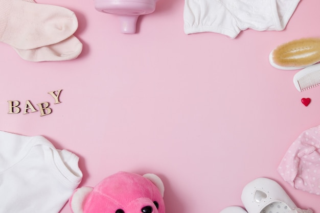 Flat lay composition with baby accessories and toys on a colored pink surface