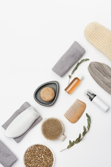 Flat lay composition with bath accessories with gel soap sea salt wooden comb on white table