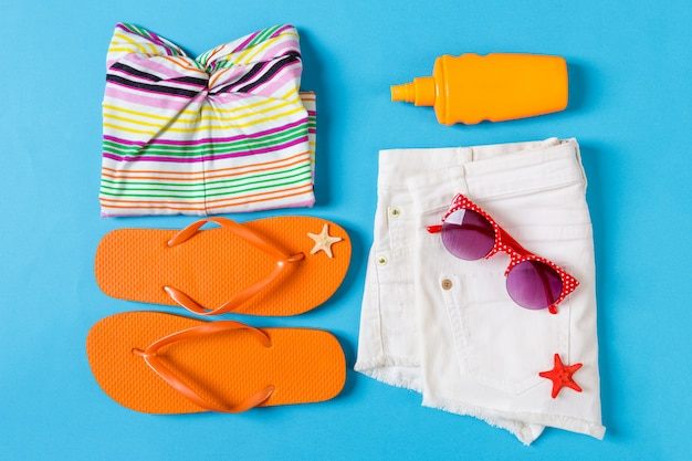 Flat lay composition with beach accessories on blue color.