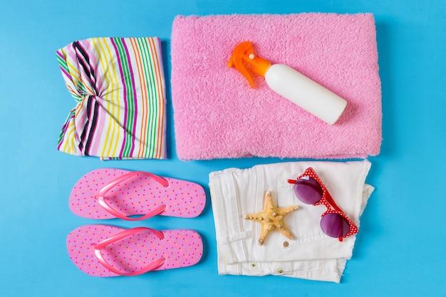 Плоская композиция с пляжными аксессуарами на синем цветном фоне. летний праздник фон. вид сверху на отпуск и путешествия.