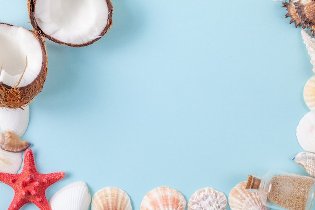 Flat lay composition with beautiful sea elements and coconut on a blue background