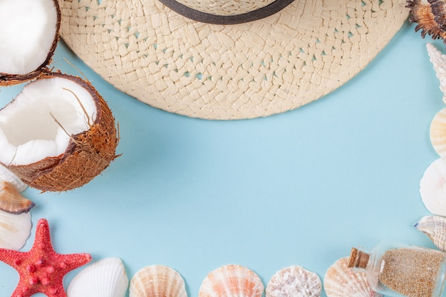 Flat lay composition with beautiful sea elements and straw hat on a blue background