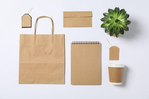 空白の文房具、紙袋、白い背景の上の多肉植物とフラットレイアウト構成