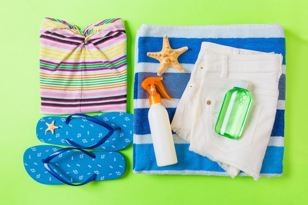 緑の色の背景に青いビーチアクセサリーとフラットレイ構成。夏休みの背景。休暇や旅行のアイテムの上面図。