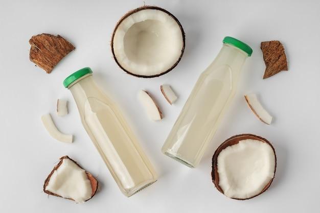 Плоская композиция с бутылками кокосовой воды и орехами на белом фоне