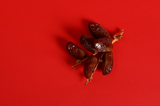 Flat lay composition with a branch of fresh tasty sweet dates for breakfast after interruption and fasting in ramadan