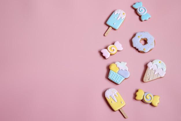 분홍색 배경 복사 공간에 밝은 글레이즈 진저 브레드 쿠키가 있는 평평한 구성.