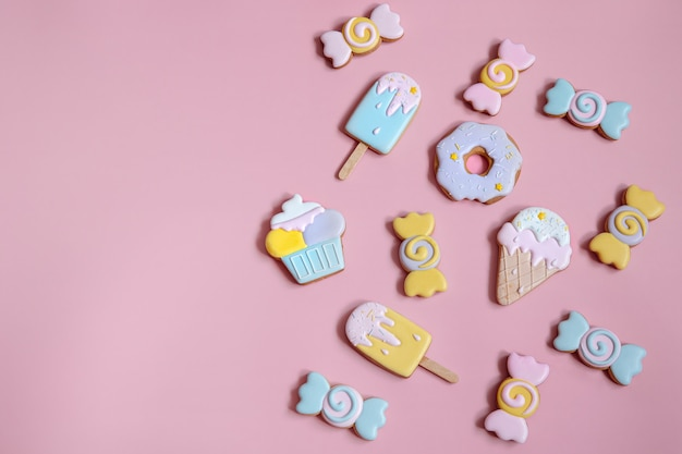 Flat lay composition with bright glazed gingerbread cookies on pink background copy space.
