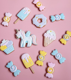 Flat lay composition with bright glazed gingerbread cookies on pink background.