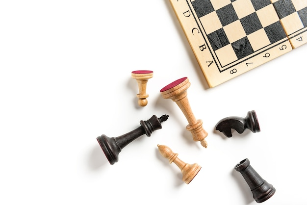 Flat lay composition with chess pieces and chessboard isolated on white background