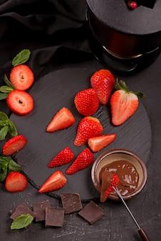 灰色の背景にチョコレートで覆われたイチゴとフラットレイ構成