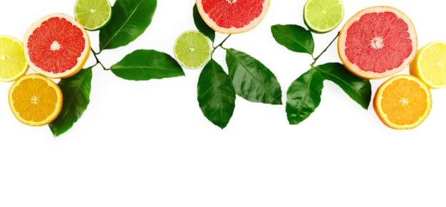 白い背景、コピースペース、バナーに柑橘系の果物、葉、花とフラットレイ構成。