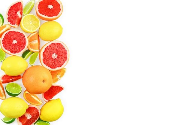 白い背景、コピースペースに柑橘系の果物、葉、花とフラットレイ構成。