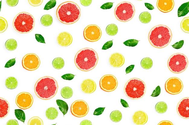 白い背景、シームレスなパターンに柑橘系の果物、葉、花とフラットレイ構成。