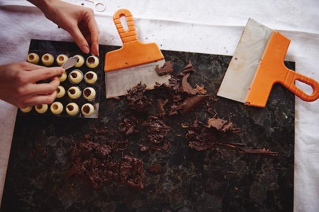 ホワイトチョコレートから球形の型にチョコレートの詰め物を入れる菓子職人の手によるフラットレイ組成物。大理石の表面に横たわっている強化チョコレートの塊とスクレーバー
