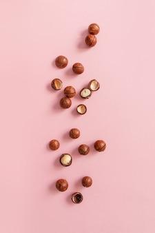Плоская композиция с треснувшими орехами макадамия на розовом