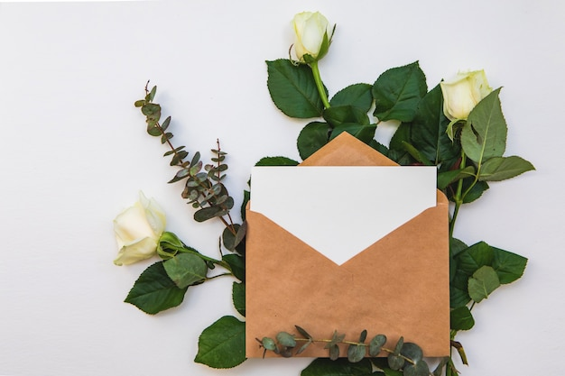 Flat lay composition with a craft paper envelope, blank card and a white rose flowers. mockup for romantic wedding or valentine's day note. top view.