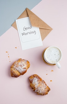 Flat lay composition with cup of coffee, croissants and postcard with text good morning