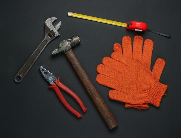 Плоская композиция с различными промышленными рабочими инструментами и инструментами, защитное оборудование на черном фоне. вид сверху