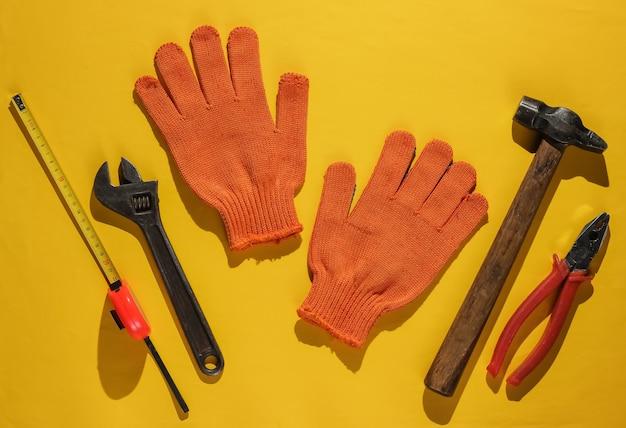 さまざまな産業用作業ツールと機器、黄色の背景に安全装置を備えたフラットレイ構成。上面図