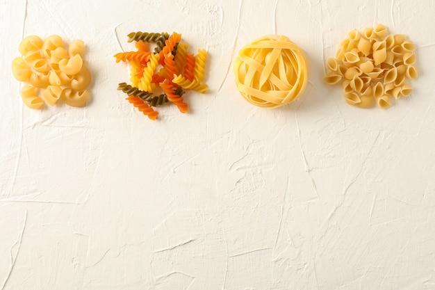 Плоский лежал композиция с различными макаронами на белом фоне, пространство для текста. сухие сырые целые макароны