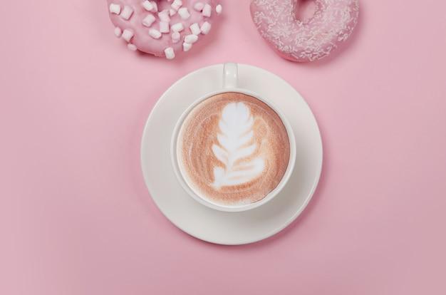 ピンクの背景にドーナツとコーヒーのカップとフラットレイ構成