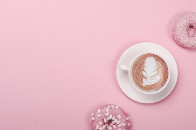 분홍색 배경에 도넛과 커피 한잔과 평면 위치 구성