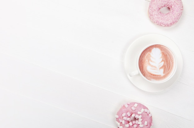 Flat lay composition with donuts and cup of coffee on white background