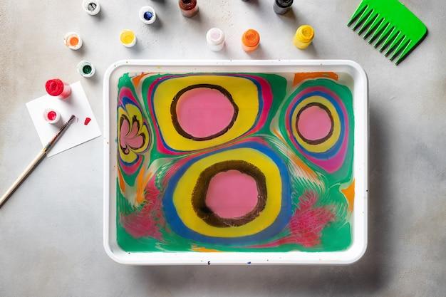 墨流しの描画とテーブル上のツールを使用したフラットレイ構成