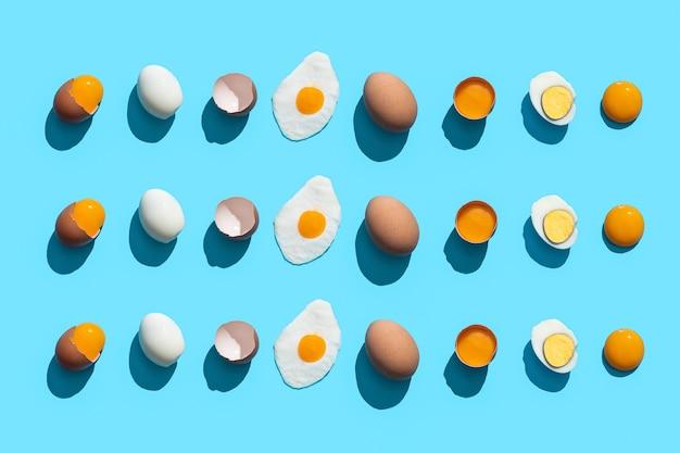 Композиция flat lay с яйцами, приготовленными по-разному на синем фоне.