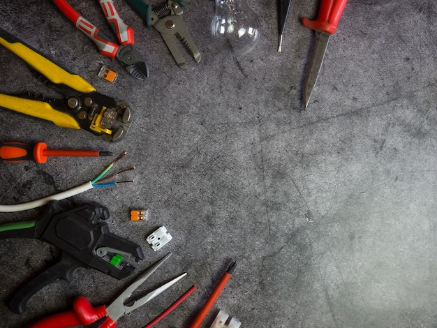 Flat lay composition with electrician's tools and space for text on gray concrete background
