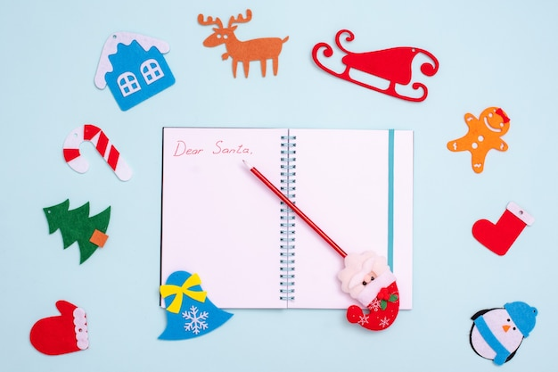 Flat lay composition with an empty open notebook with the inscription dear santa, a pen with santa claus and felt christmas decorations