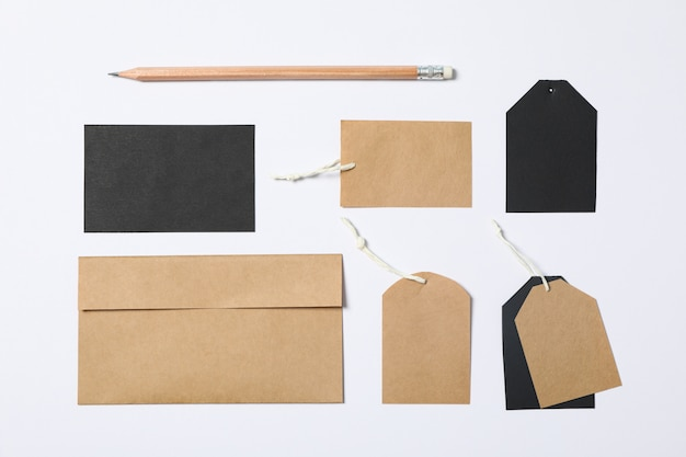 Flat lay composition with envelope, tags and pencil on white background