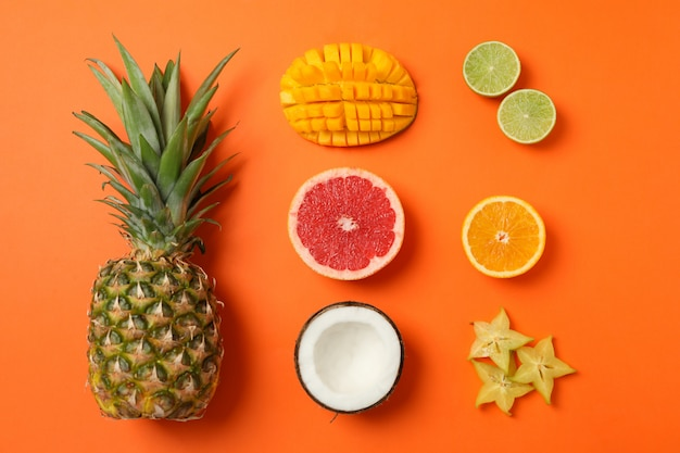 Flat lay composition with exotic fruits on orange, top view